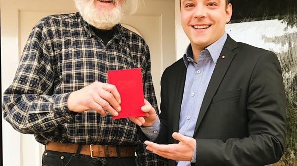 Lutz Kitze erhält sein neues SPD-Parteibuch von Maximilian Schmidt überreicht